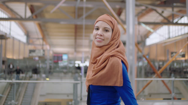 vidéos et rushes de slo mo. portrait of middle eastern female traveler walking through airport terminal near entrance. - confiance en soi