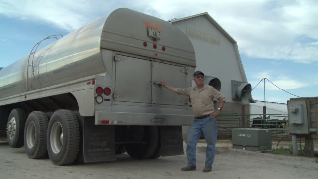ms portrait of milk tank driver leaning against his truck outside dairy farm, newark, illinois, usa - milkman stock videos & royalty-free footage