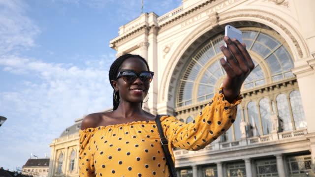 vídeos de stock, filmes e b-roll de retrato do turista africano milenar com cabelo trançado que toma selfies-câmera handheld - atividade móvel