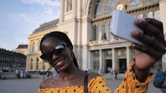vídeos de stock e filmes b-roll de portrait of millennial african tourist with braided hair taking selfies - handheld camera - braided hair