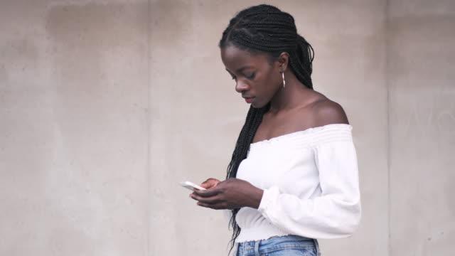 vídeos de stock e filmes b-roll de portrait of millennial african woman with braided hair using mobile phone - handheld camera - braided hair