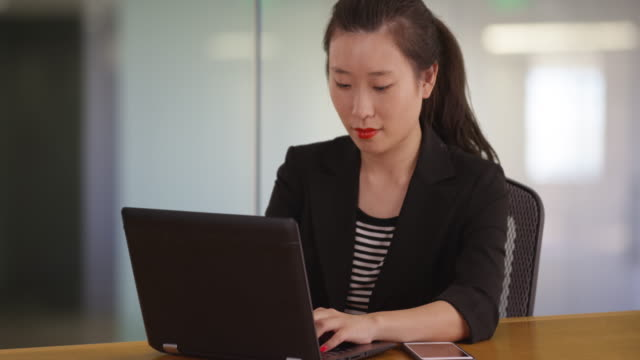 Portrait of millennial businesswoman typing on laptop computer in office studio