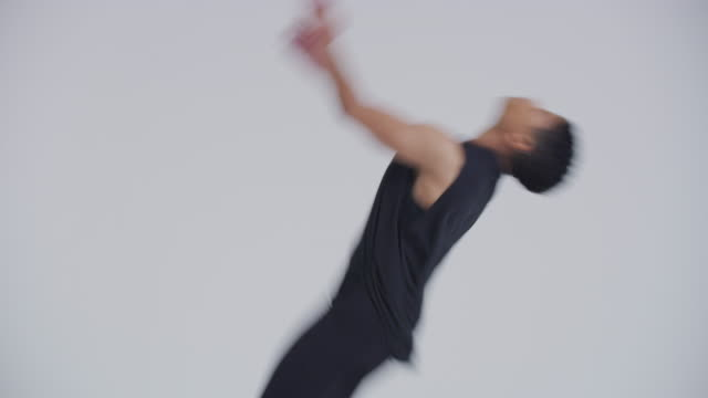 portrait of modern dancer, acrobat, woman back flipping in studio dressed in black - バク転点の映像素材/bロール
