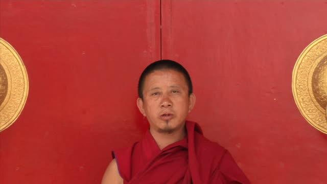 cu, zo, ws, portrait of monk standing at tibetan monastery, bodh gaya, bihar, india - monk stock videos & royalty-free footage