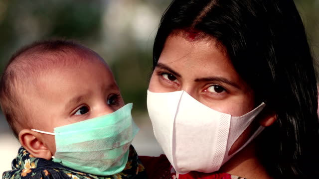 portrait of mother and baby daughter covering face with pollution mask against covid-19 or coronavirus - pollution mask stock videos & royalty-free footage