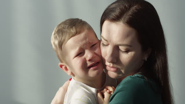 portrait of mother and crying child shot indoors on red camera - trösten stock-videos und b-roll-filmmaterial
