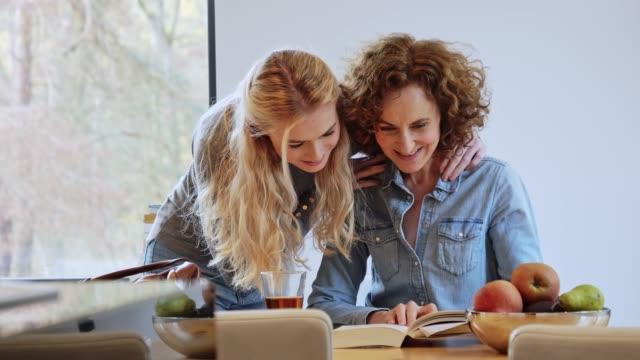 vídeos de stock, filmes e b-roll de retrato da matriz e da filha que bebem o chá quente e o livro de leitura - espontânea