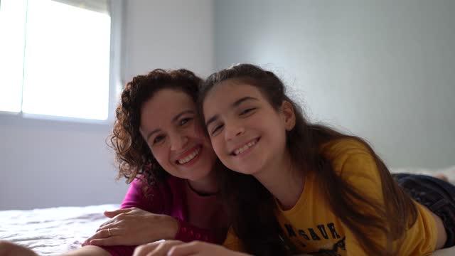 vídeos de stock, filmes e b-roll de retrato de mãe e filha usando celular na cama em casa - aconchegante