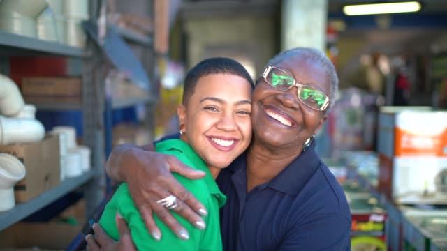 vídeos de stock, filmes e b-roll de retrato da matriz e da filha que trabalham junto em uma loja da pintura - família de duas gerações