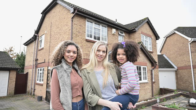 portrait of mother and daughters in front of family home - facade stock videos & royalty-free footage
