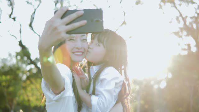 Portrait of mother and her daughter girl using smartphone for selfie at park. Laughing mom and daughter posing for camera in sunset time on summer day