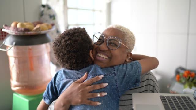 vídeos de stock, filmes e b-roll de retrato de mãe e filho abraçados em casa - cozinha doméstica