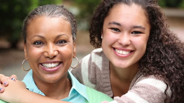 Portrait of mother and teenager daughter smiling