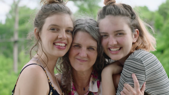 MS SLO MO. Portrait of mother and two daughters smiling at camera.