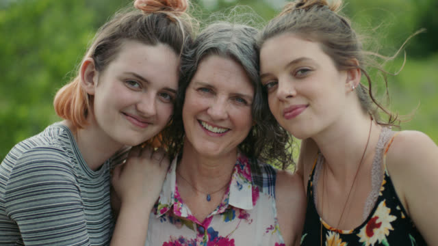 vidéos et rushes de ms slo mo. portrait of mother and two daughters smiling at camera. - femme mure