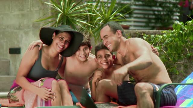 ms portrait of mother, father and tree children (7-12) embracing by pool, panama city, panama  - 12 13 år bildbanksvideor och videomaterial från bakom kulisserna