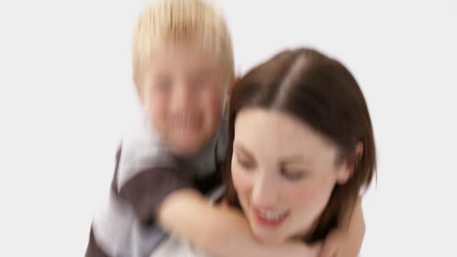 vídeos de stock, filmes e b-roll de cu portrait of mother giving son (4-5) piggyback ride in studio / cape town, western cape, south africa - áfrica meridional