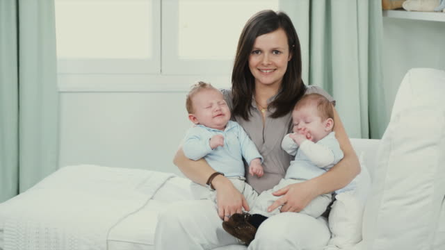 MS Portrait of mother holding twin boys (2-5 months) on lap sitting on chaise lounge, Brussels, Belgium