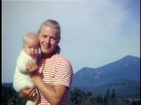 vidéos et rushes de 1963 ms portrait of mother with baby girl, mountains in background, vermont, usa - cheveux blonds