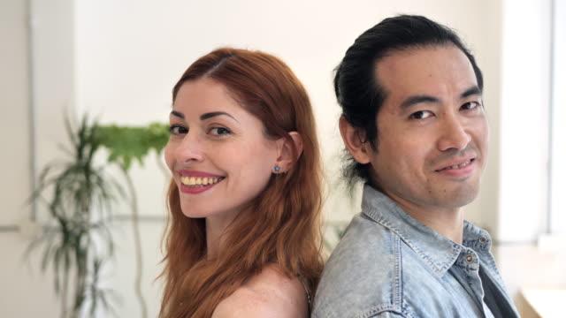 porträt von multiethnischen paar - japanisch und latina stehen zurück und lächelnd - rotes haar stock-videos und b-roll-filmmaterial