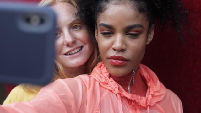 portrait of multiethnic women taking selfie, close up - 口を尖らせる点の映像素材/bロール