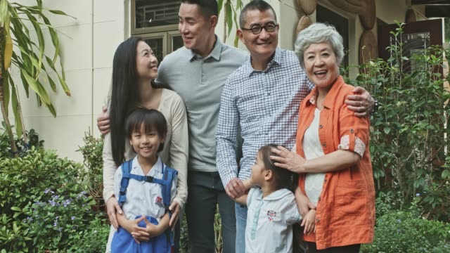 portrait of multi-generational chinese family standing in the backyard garden at home - multi generation family stock videos & royalty-free footage