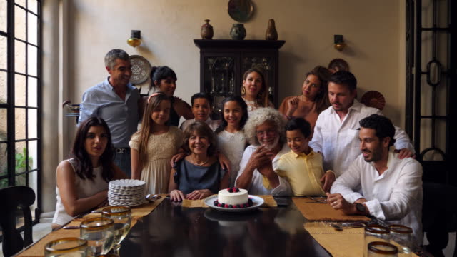vidéos et rushes de ws portrait of multigenerational family gathered in dining room during celebration dinner - latino américain