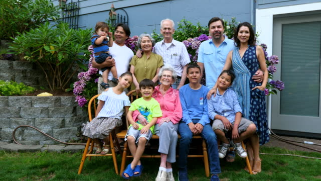 ms portrait of multigenerational family in backyard garden on summer evening - kleid stock-videos und b-roll-filmmaterial
