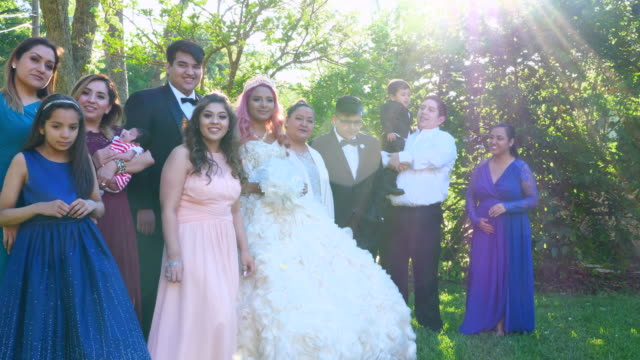 stockvideo's en b-roll-footage met ms portrait of multigenerational family standing in backyard with young woman dressed in quinceanera gown - 10 11 jaar