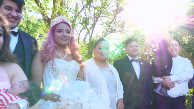 ms pan portrait of multigenerational family standing in backyard with young woman dressed in quinceanera gown - 14 15 anni video stock e b–roll
