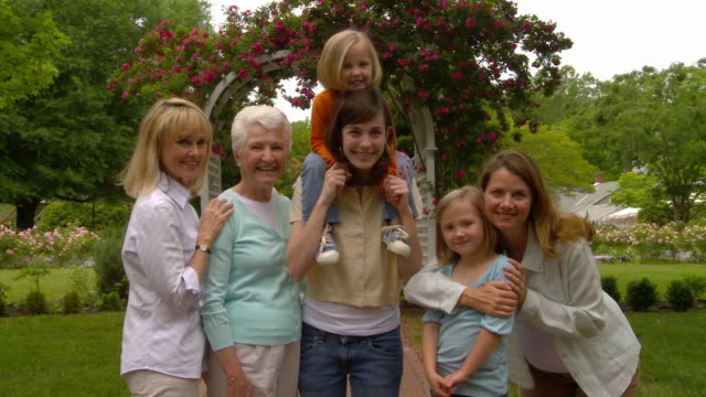 MS Portrait of multigenerational group of women standing and smiling outdoors / Richmond, Virginia