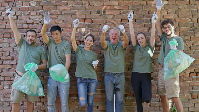 portrait of multiracial volunteers with garbage bags in front brick wall after environmental cleanup - gardening glove stock videos & royalty-free footage