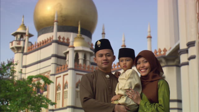 ms, portrait of muslim family with son (2-3) in front of mosque, singapore - familie mit einem kind stock-videos und b-roll-filmmaterial