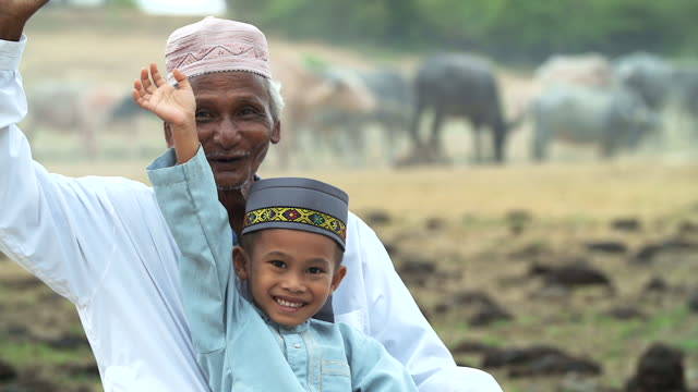 Portrait of muslim grandfather and grandchild with smiley face.