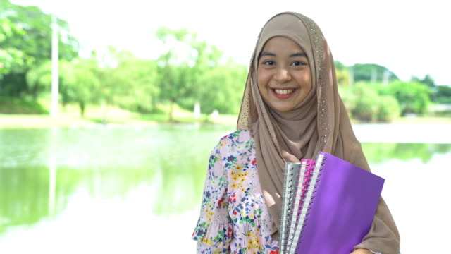 portrait of muslim teenager university student with book - indonesian culture stock videos & royalty-free footage