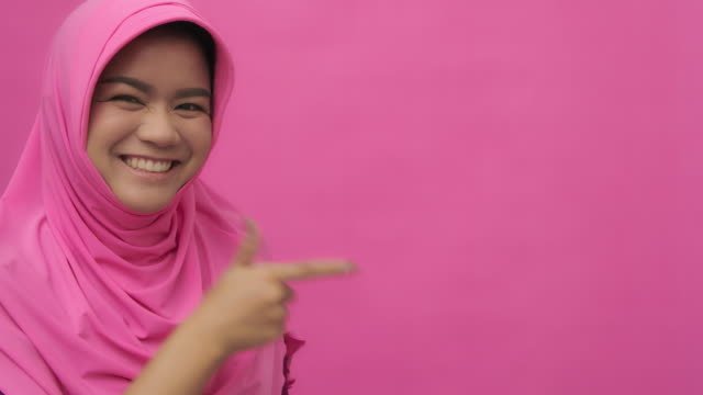 slo mo portrait of muslim woman with hand gesture pointing at your logo-pink background copy space - pointing stock videos & royalty-free footage