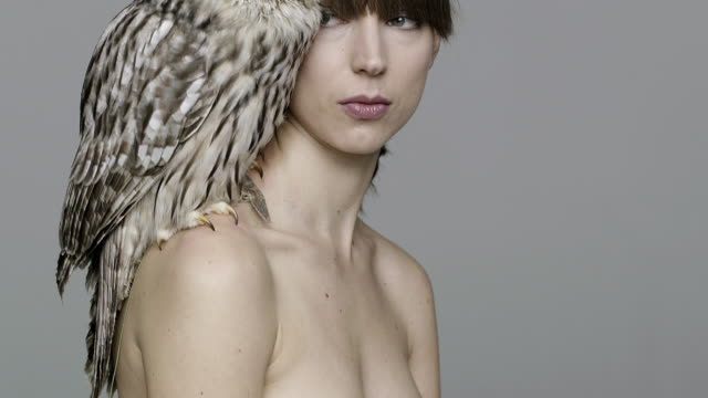 portrait of nude woman with owl on shoulder - fkk stock-videos und b-roll-filmmaterial