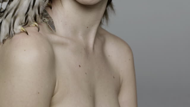 portrait of nude woman with owl on shoulder