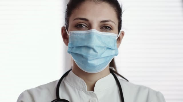portrait of nurse wearing face mask in workplace. 4k stock video - prevenzione delle malattie video stock e b–roll
