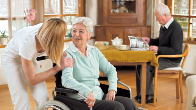 DS Portrait of nurse with senior woman in wheelchair
