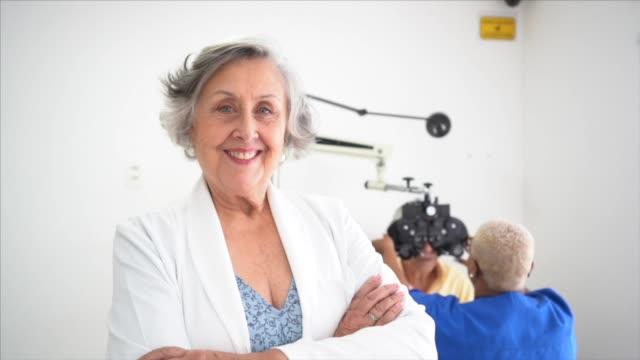 portrait of opthamologist senior female doctor at clinic - eyesight stock videos & royalty-free footage