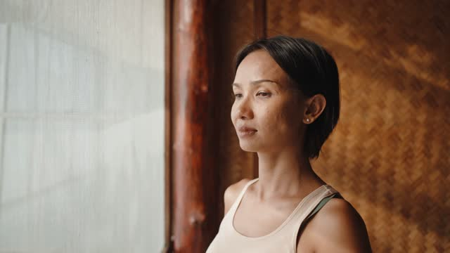 portrait of pensive woman standing by the window - one mid adult woman only stock videos & royalty-free footage