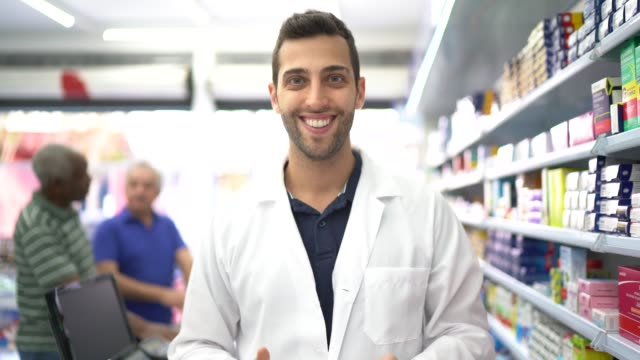 portrait of pharmacist in a drugstore, customers in the background - pharmacy stock videos & royalty-free footage