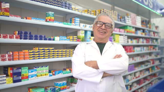 portrait of pharmacist in a drugstore - arms crossed stock videos & royalty-free footage