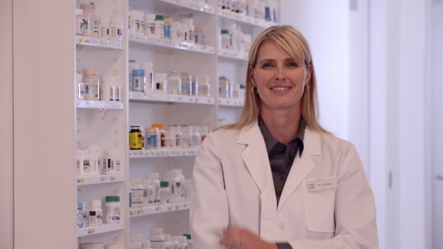 stockvideo's en b-roll-footage met ms pan portrait of pharmacist in front of medication bottles / richmond, virginia, usa - apotheker