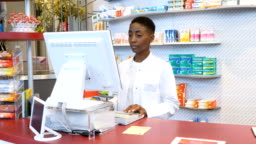 Portrait of pharmacist using computer in store