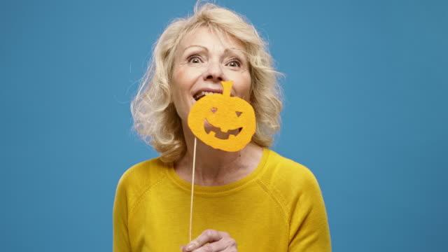 stockvideo's en b-roll-footage met portret van speelse rijpe vrouw met de steunen van halloween - blauwe achtergrond