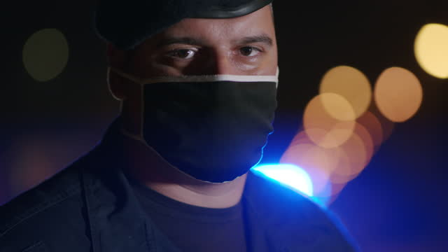 vídeos de stock, filmes e b-roll de retrato de policial com máscara facial em frente a carros de patrulha - força policial