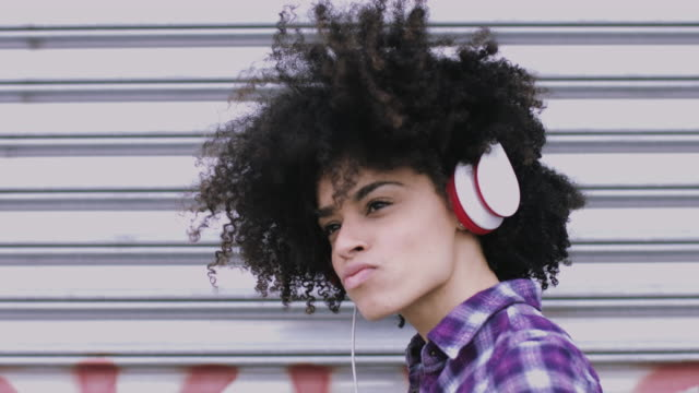 Portrait of pretty Afro American Female on street looking listening to music on headphones