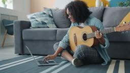Portrait of pretty Afro-American girl playing the guitar and using laptop at home
